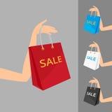 红色购物袋在妇女的手和三上 免版税库存图片