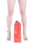 红色购物袋特写镜头在美好的妇女腿之间的 免版税库存图片