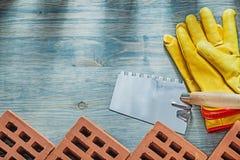 红色建筑砖用皮革包盖安全手套调色刀buil 免版税库存图片