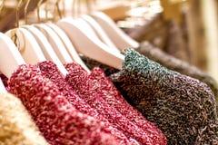 红色黄色编织了垂悬在挂衣架的毛线衣 图库摄影