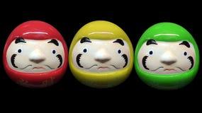 红色绿色黄色颜色daruma玩偶在黑孤立背景中 免版税库存图片