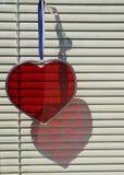 红色刻花玻璃心脏反射在与窗帘的一个窗口里 免版税库存图片