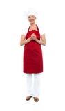 红色围裙和无边女帽的可爱的女性厨师 免版税库存图片