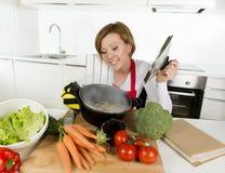 红色围裙的家庭厨师妇女在举行烹调的国内厨房罐用热的汤嗅到的菜炖煮的食物 免版税图库摄影