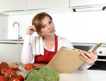 红色围裙的年轻美丽的家庭厨师妇女在现代国内厨房读书菜谱在食谱后 免版税库存图片