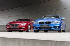 红色640i和蓝色425d湿在雨BWM汽车以后 免版税图库摄影