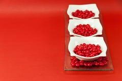 红色3个糖果的盘 库存图片