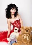 红色ccorset的年轻和美丽的妇女坐与玩具熊的一个地板 免版税库存照片