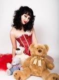 红色ccorset的年轻和美丽的妇女坐与玩具熊的一个地板 库存图片