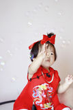 红色cheongsam戏剧肥皂泡的滑稽的中国矮小的婴孩 免版税库存图片