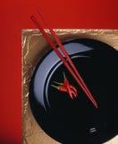 红色chillis和筷子在黑色的盘子 免版税库存照片