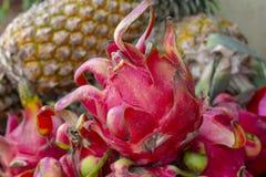 红色dragonfruit和菠萝在市场桌上 在自然农厂市场上的热带水果 有机水多的异乎寻常的果子 免版税图库摄影