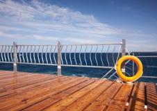 红色lifebuoy与在一个木码头的绳索 免版税库存照片