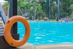 红色lifebuoy在一个公开游泳池附近 免版税库存照片