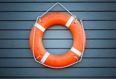 红色lifebuoy垂悬在蓝色木墙壁上 免版税库存照片