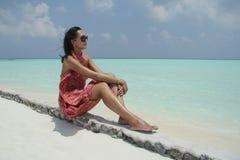 红色pareo的被晒黑的女孩在Maldivian海滩 免版税库存图片