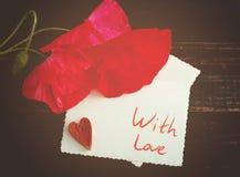 红色poppys和白色卡片题字`的与爱`和装饰心脏 免版税库存图片