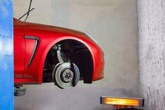 红色sportcar在轮胎和轮子替换的服务站 免版税库存照片