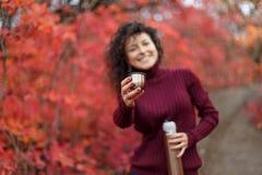 红色sweather的年轻黑发妇女与在红色autumnn灌木的热水瓶提供喝一个杯子热的饮料 免版税库存图片