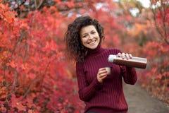 红色sweather的年轻黑发妇女与在红色autumnn灌木的热水瓶 库存照片