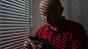 红色T恤杉卷动的人通过关于手机的信息在办公室 影视素材