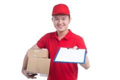 红色T恤杉和盖帽微笑的英俊的年轻工人,举行a 免版税库存照片