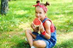 红色T恤杉的在拿着一个成熟西瓜的牛仔布总体的女孩和头巾 库存图片