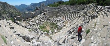 红色T恤杉的游人在古老剧院站立在Termessos 图库摄影