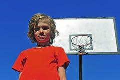 红色T恤杉的男孩有在背景的篮球篮的 免版税库存照片