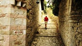 红色T恤杉的男性旅客在古老地中海堡垒走在度假 免版税图库摄影