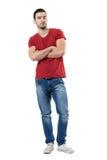 红色T恤杉的骄傲的年轻偶然时髦人用看照相机的横渡的手 免版税图库摄影