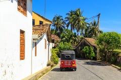 红色tuk-tuk在鹅卵石路面站立在有一个铺磁砖的屋顶的房子附近在一个小热带镇在一个清楚的晴天中间 免版税库存照片