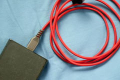 红色USB缆绳和黑powerbank 免版税库存照片