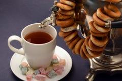 红茶俄国式茶炊在黑暗的背景的葡萄酒金属以百吉卷土耳其快乐糖 库存图片
