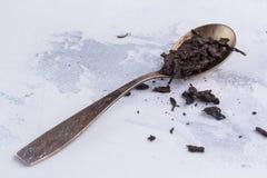红茶叶子在一把匙子的在白色背景 在一把古色古香的匙子的茶 库存图片