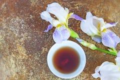 红茶杯子虹膜花石头背景没人 免版税库存图片