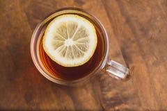 红茶顶视图用在木板条桌上的柠檬 免版税库存照片