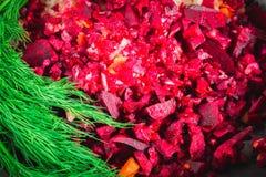 红萝卜、甜菜和葱在一个煎锅,在莳萝附近,在棕色木背景 罗宋汤的成份 免版税库存图片