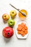 红萝卜、石榴和苹果用蜂蜜犹太新年 免版税库存图片