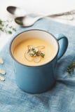 从红萝卜和土豆的菜奶油色汤装饰了在蓝色碗的杏仁剥落在土气背景 库存图片