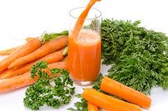 红萝卜汁涌入了玻璃 库存图片