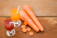 红萝卜汁玻璃和新鲜的红萝卜在木背景在夏日-选择聚焦 免版税图库摄影
