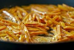 红萝卜裁减成小条和油煎在平底锅 库存图片