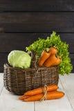 红萝卜,圆白菜,在一个wattled篮子的莴苣在一张木桌上 图库摄影