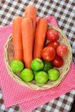 红萝卜,蕃茄,在篮子的石灰 免版税库存图片
