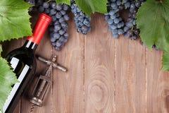 红葡萄、酒瓶和拔塞螺旋 免版税库存图片