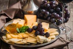 红葡萄酒、葡萄和乳酪被提炼的静物画  免版税库存图片