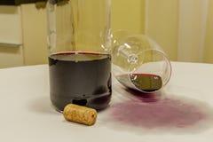 红葡萄酒从在白色桌布的玻璃溢出与的瓶 免版税图库摄影