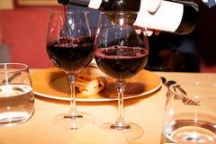 红葡萄酒和两块玻璃在桌上 库存图片