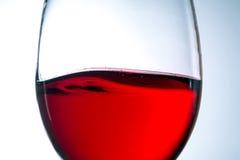 红葡萄酒波浪在玻璃特写镜头的 库存照片